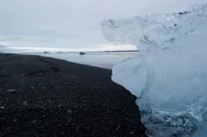 blaues Eis und schwarzer Sand